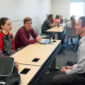 Students speaking to a professor in a classroom