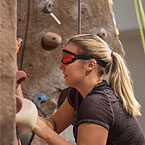 student wearing a blindfold while rock climbing